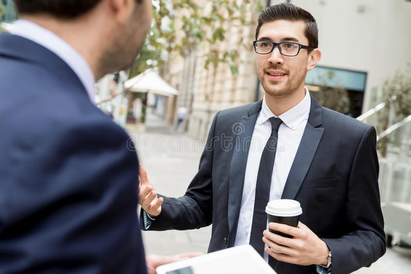 Two businessmen talking outdoors. While taking coffee break royalty free stock photo