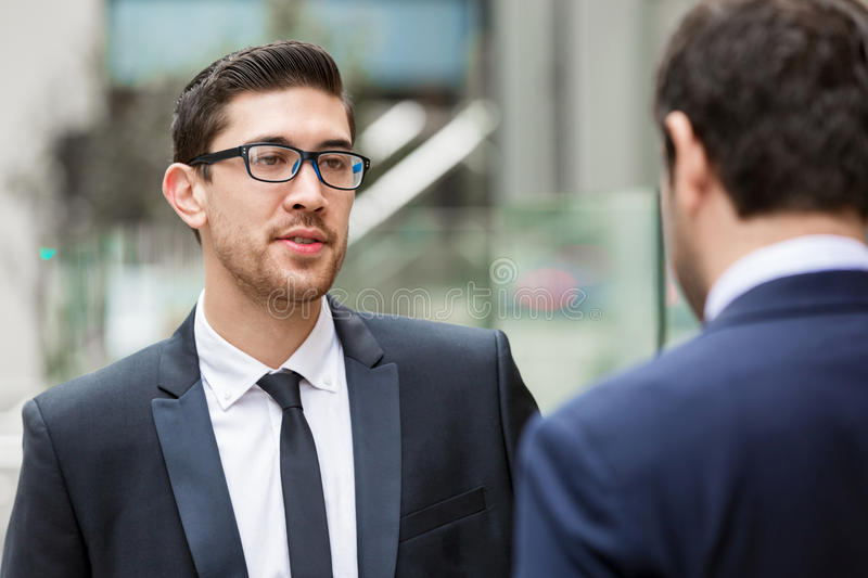 Two businessmen talking outdoors. While taking coffee break stock photography