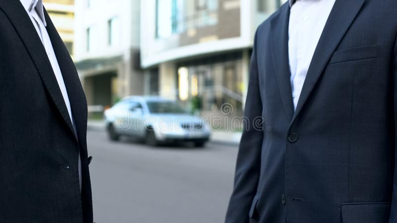 Two businessmen talking outside office building, discussing financial deal stock images