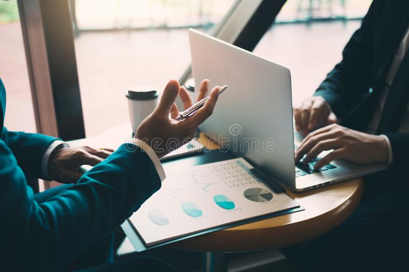 Two businessmen are talking about the results of operations in the company financial statements on the computer screen.  royalty free stock image