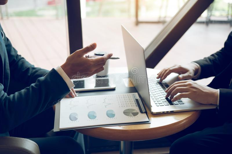 Two businessmen are talking about the results of operations in the company financial statements on the computer screen.  stock image