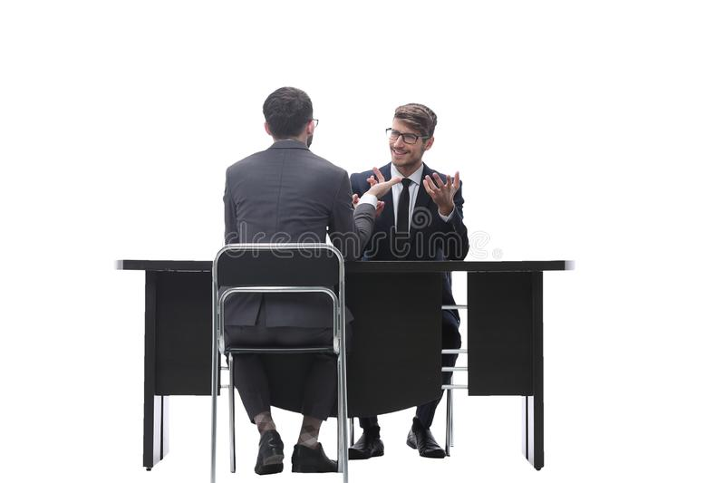 Two businessmen talking, sitting at his Desk. Isolated on white background stock image
