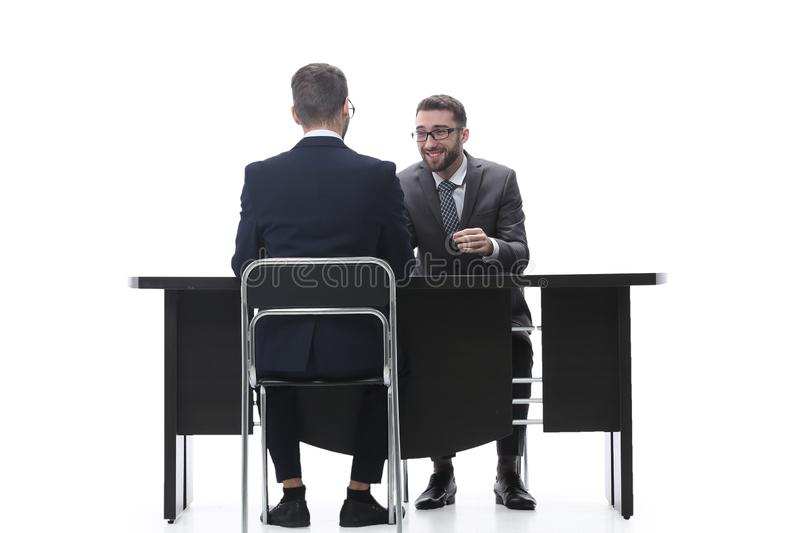 Two businessmen talking, sitting at his Desk. Isolated on white background royalty free stock photo