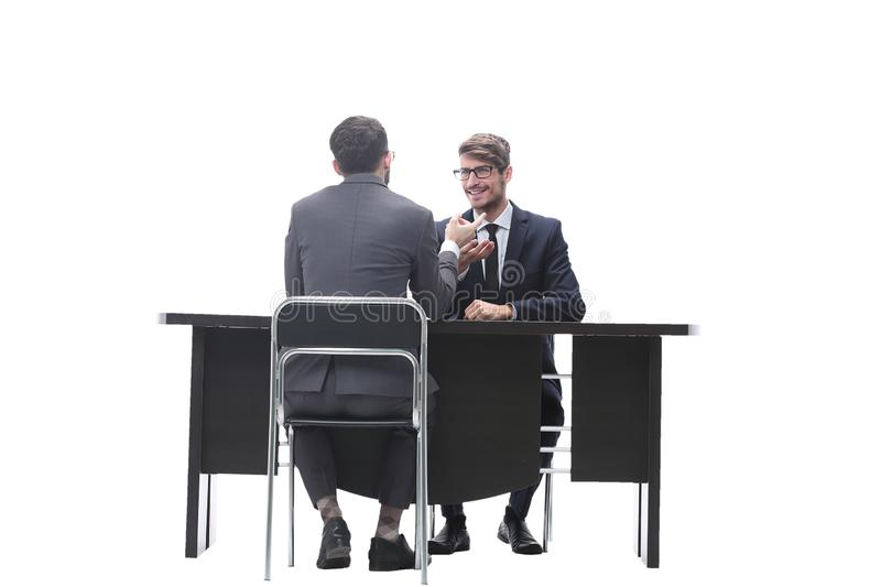 Two businessmen talking, sitting at his Desk. Isolated on white background royalty free stock image