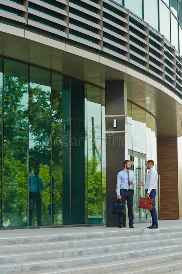 Two Businessmen talking on Steps of Modern Business Center royalty free stock photography