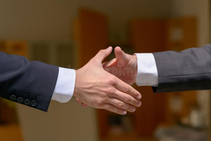 Two businessmen about to shake hands stock photo
