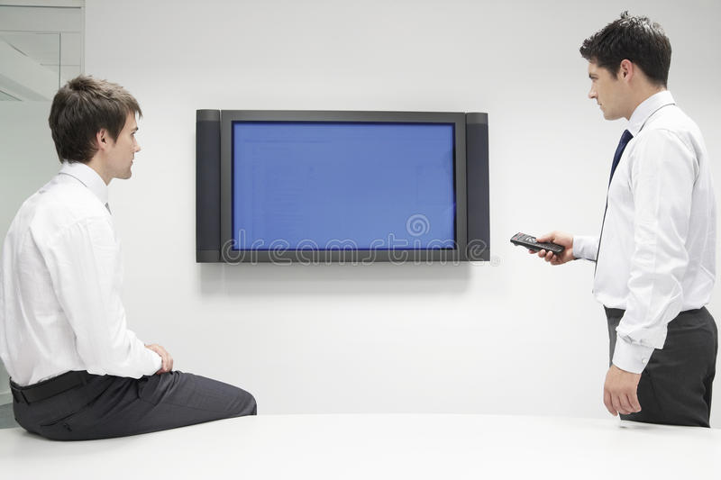 Two Businessmen Using Flat Screen Monitor. Two young businessmen using flat screen monitor while in meeting stock photo