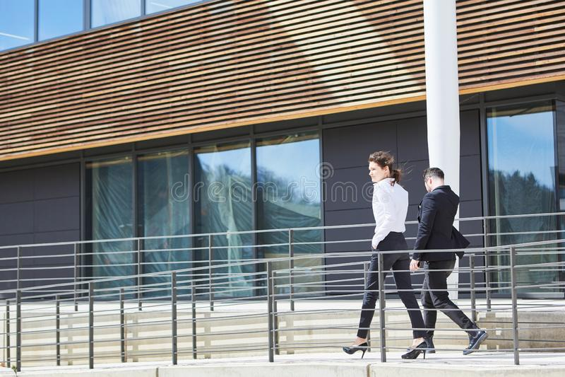 Two business people in a hurry in front of the office building royalty free stock images