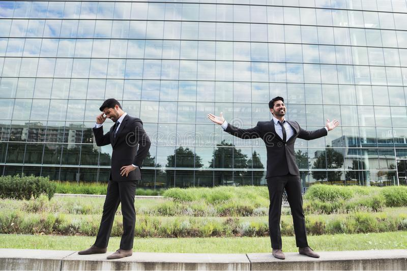 Two businessmen or workers success and failure near office building royalty free stock image