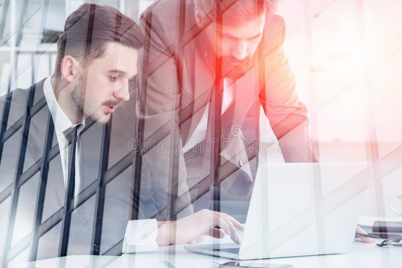 Two businessmen working with laptop in office. Two bearded young businessmen working with laptop in white office with double exposure of skyscraper. Concept of royalty free stock photography