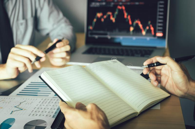 Two businessmen working together are analyzing the company`s performance graph stock photo