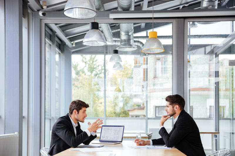 Two businessmen working together on business meeting in office. Two concentrated young businessmen working together on business meeting in office royalty free stock image