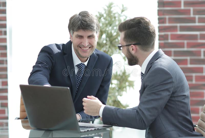 Two businessmen working together using laptop on business meeting in office royalty free stock image