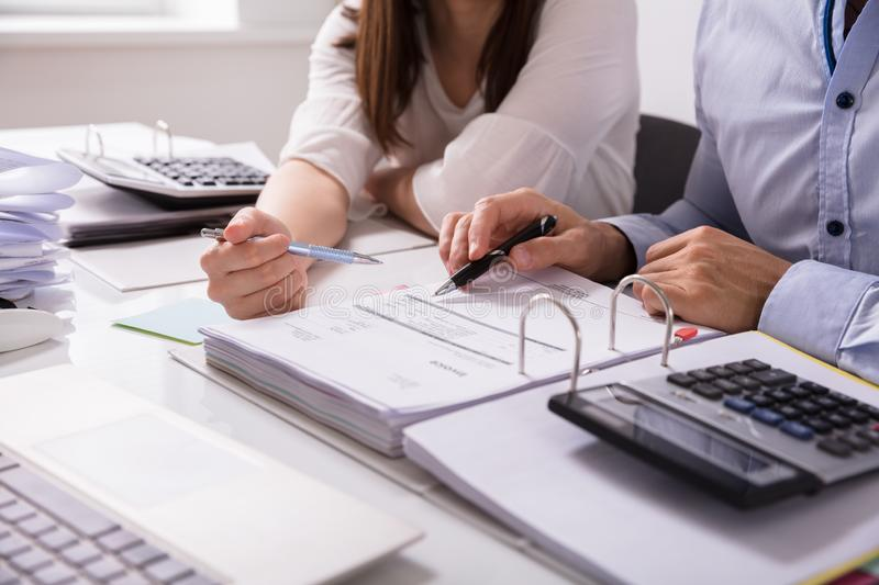 Two Businesspeople Checking Invoice. On Desk At Workplace royalty free stock images