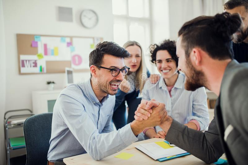 Two businesspeople with colleagues in the background in office, shaking hands. stock photo