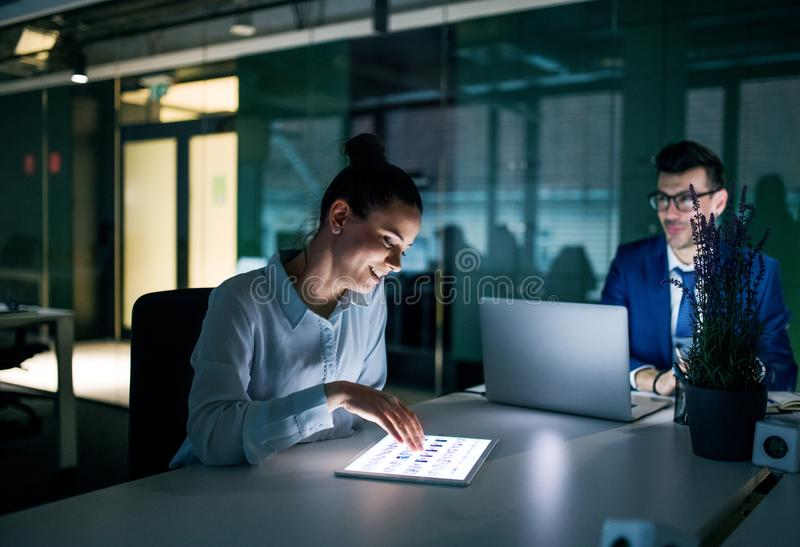 Two businesspeople with computer ssitting in an office at desk, working. Two businesspeople with a computer sitting in an office at desk, working stock photos
