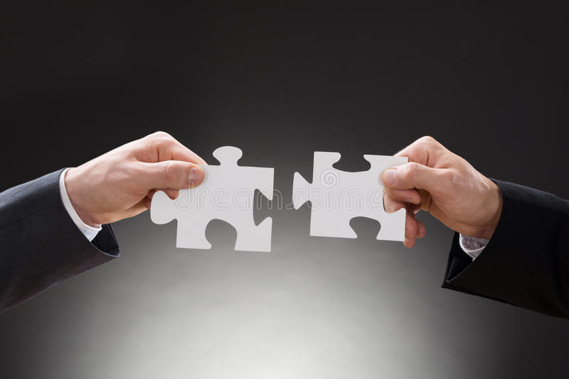 Two businesspeople holding jigsaw puzzle pieces royalty free stock photo