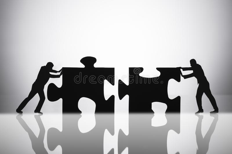 Two Businesspeople Joining Jigsaw Puzzle Pieces stock photos