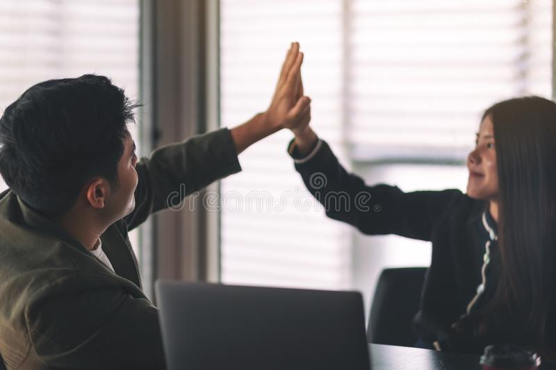 Two businesspeople putting their hands to make high five stock images