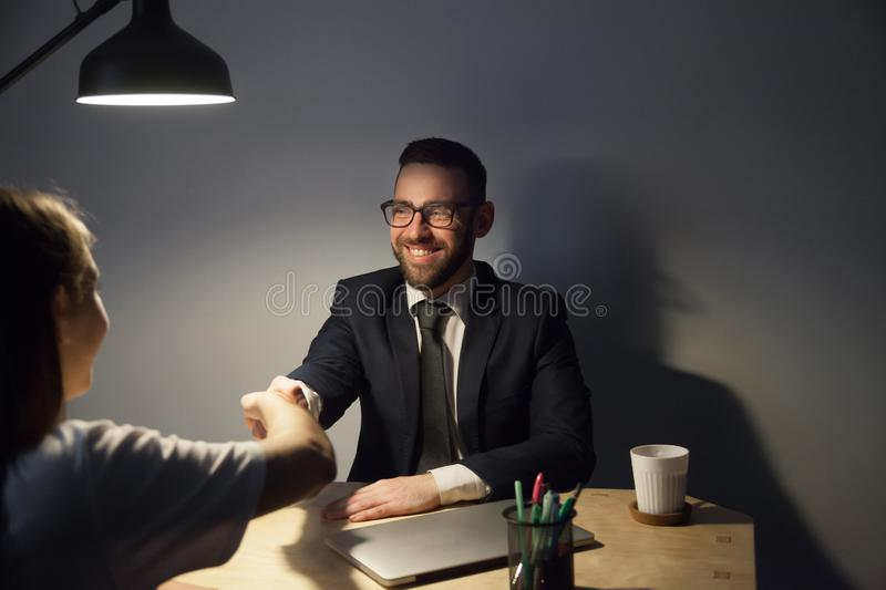 Two businesspeople seal deal in late evening meeting royalty free stock photography