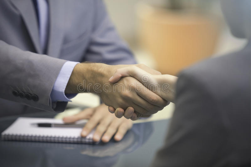 Two Businesspeople shaking hands. Indoors vector illustration