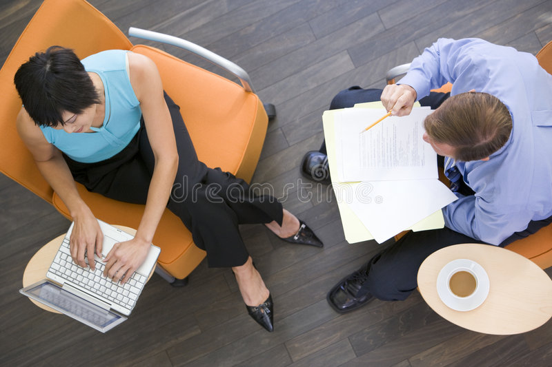 Two businesspeople sitting indoors having meeting royalty free stock photos