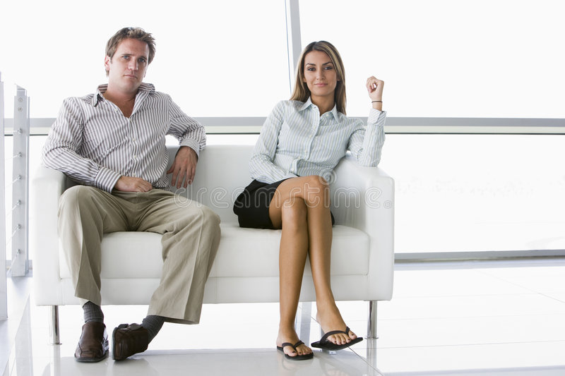 Two businesspeople sitting in office lobby smiling. Looking towards the camera stock images
