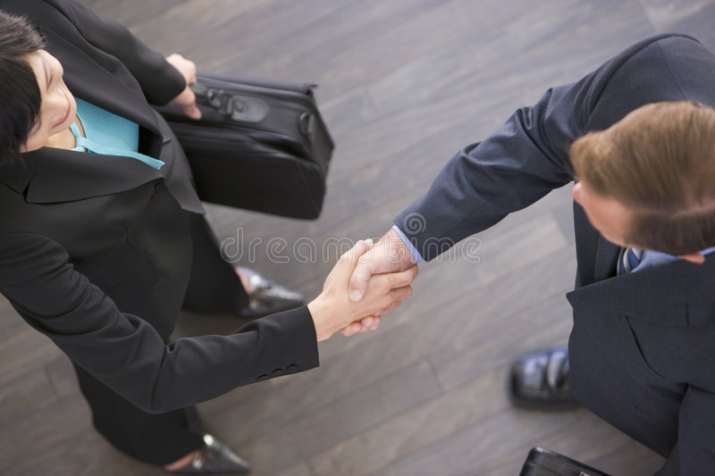 Two businesspeople standing indoors shaking hands stock image