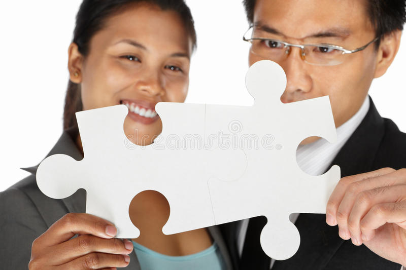 Two businesspeople sucessfuly connect the puzzle. Two Asian businesspeople successfully connect the puzzle pieces royalty free stock image