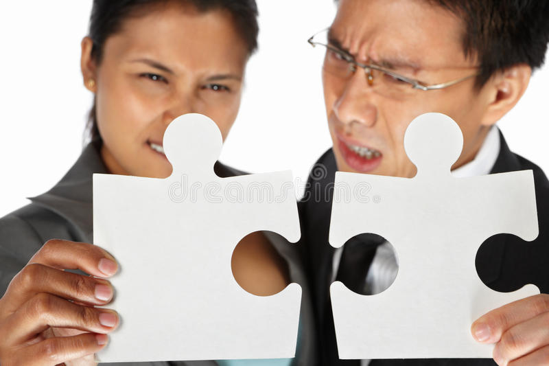Two businesspeople trying to connect the puzzle. Two Asian businesspeople trying to connect the puzzle pieces royalty free stock photography