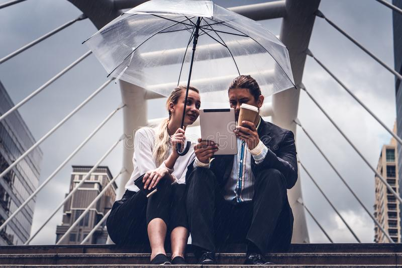 Two businesspeople with umbrella watching tablet and having business discussion in rainy season royalty free stock photos