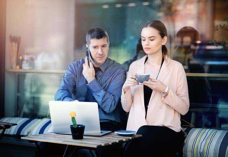 Two businesspeople working together in a local cafe. Businesspeople working together on a cafe terrace. Attractive businesswoman stock images