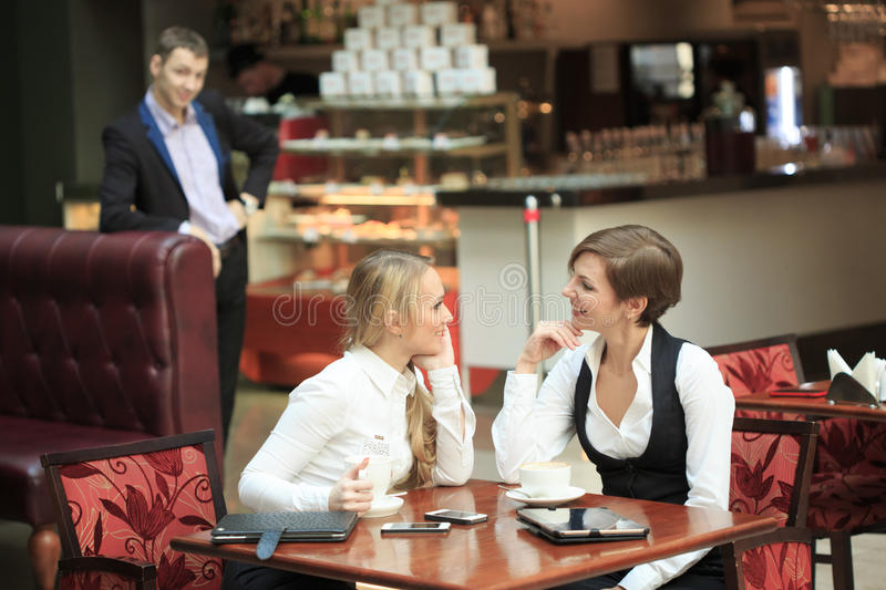 Two businesswoman in a cafe. man looking at the girls stock photo