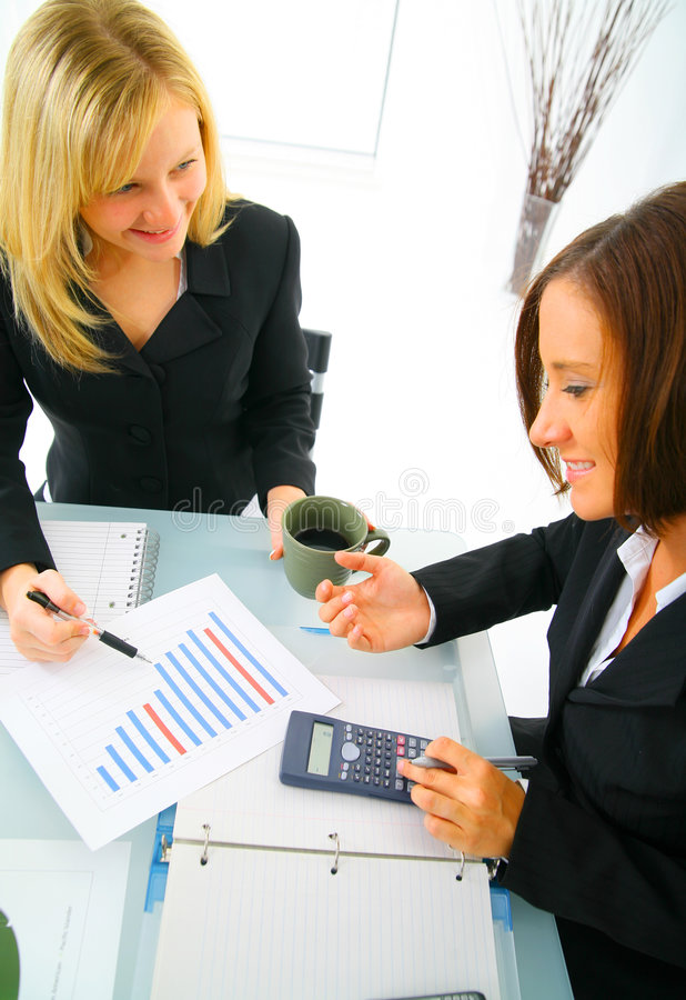 Two Businesswoman Working On Numbers. Businesswoman showing financial chart to other coworker. concept for financial, business sales, and success stock images