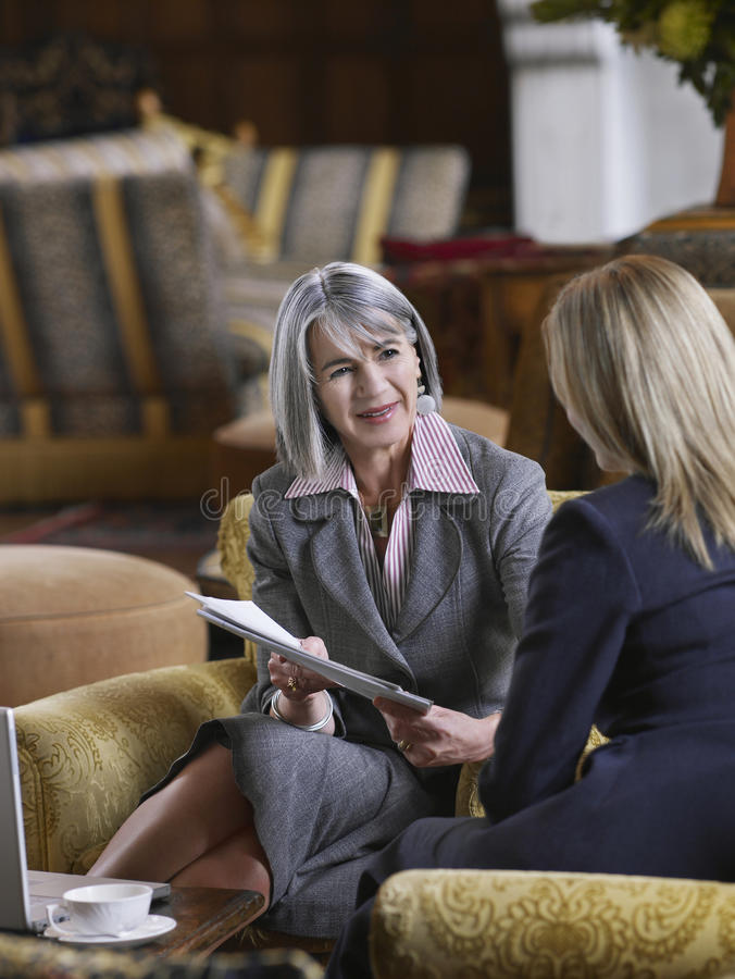 Two Businesswomen With Documents In Lobby royalty free stock photos