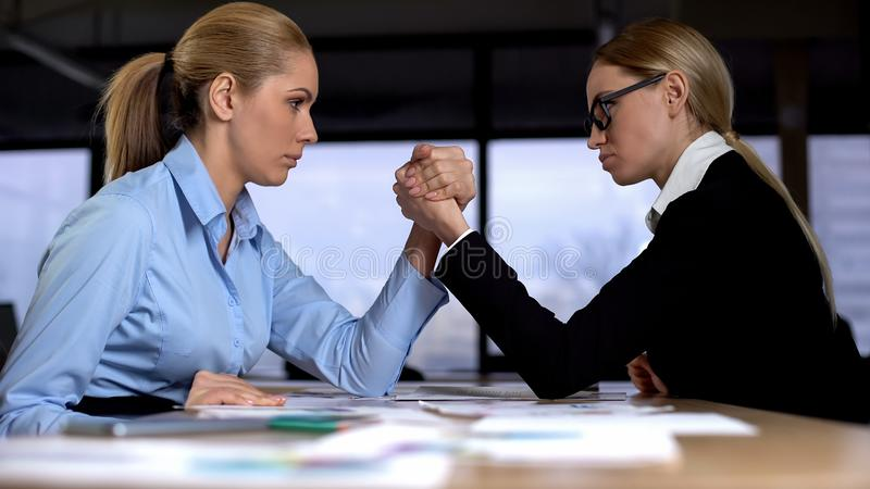 Two businesswomen doing arm wrestling in office, concept of rivalry at work stock photos