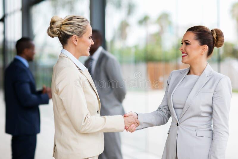 Two businesswomen handshaking royalty free stock photos