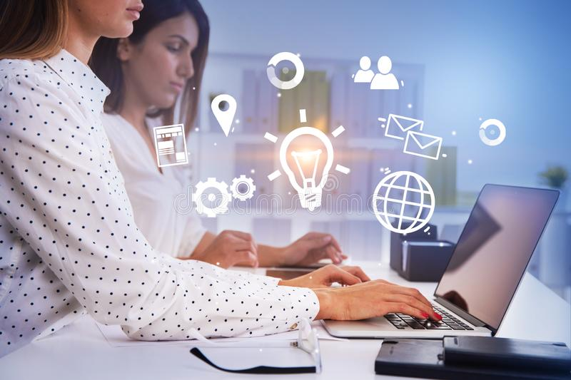 Two businesswomen in office, business idea. Side view of two young businesswomen working with laptops in modern office. Glowing business idea icons foreground stock photography