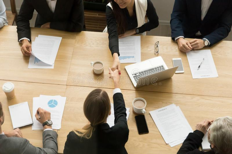 Two businesswomen shaking hands at group meeting, top view royalty free stock images