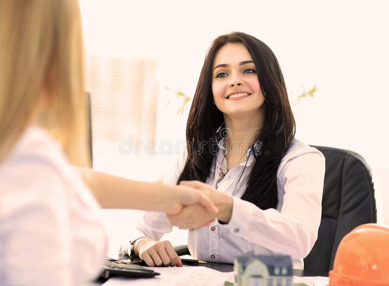 Two businesswomen shaking hands in modern office. stock photography