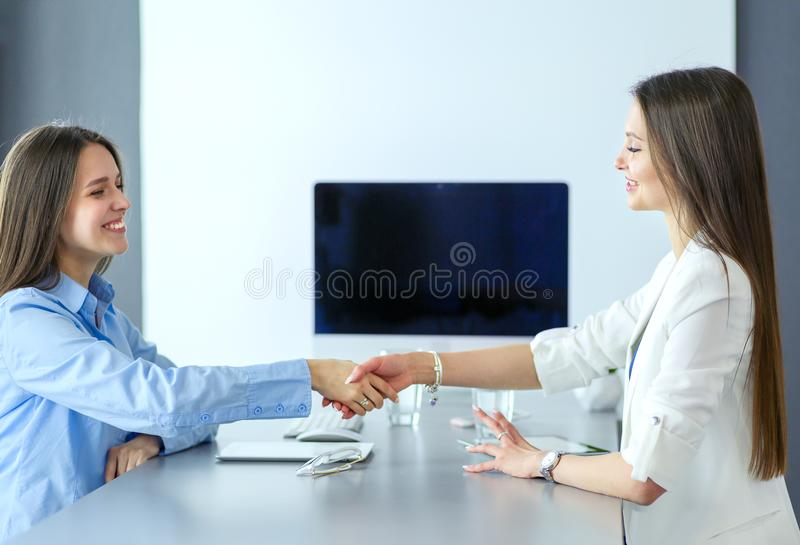 Two businesswomen sitting at a desk shaking hands stock image