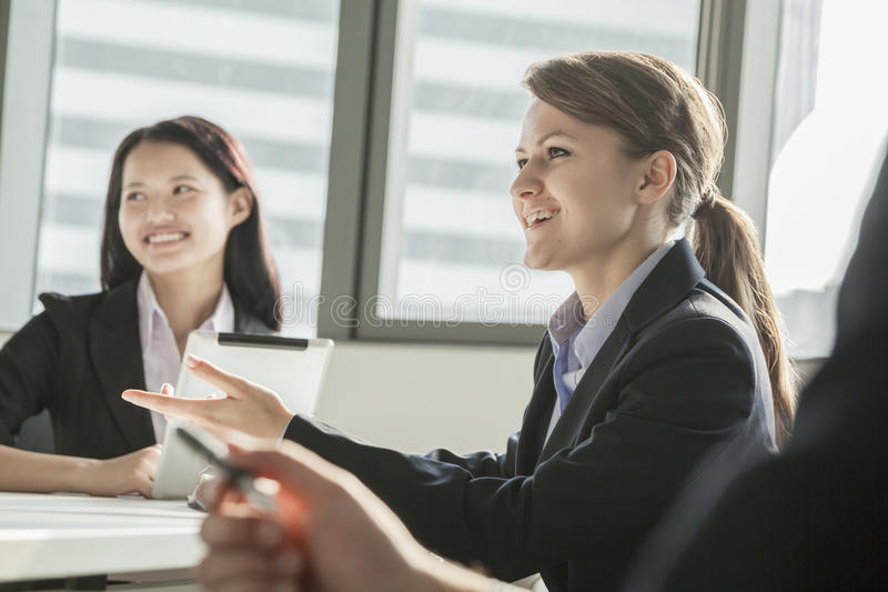 Download Two Businesswomen Smiling, Discussing, And Gesturing During A Business Meeting Stock Image - Image: 33403049
