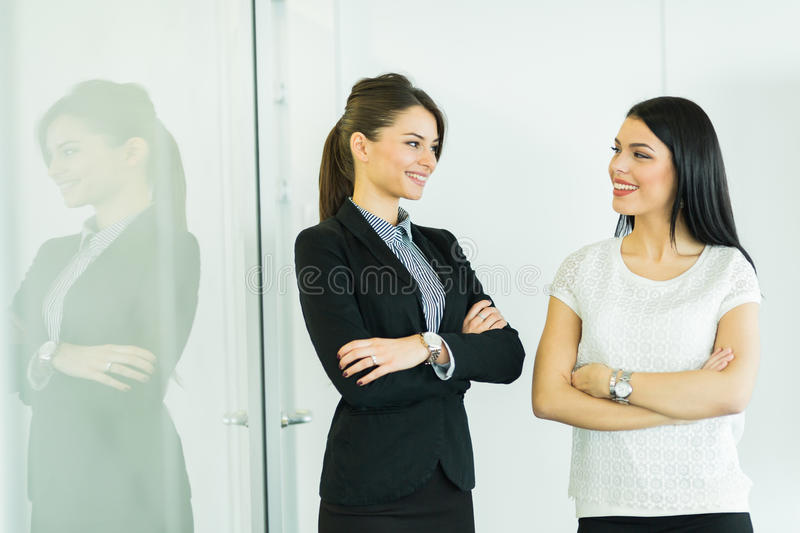 Two businesswomen talking in an office with reflection. On the glass behind them royalty free stock image
