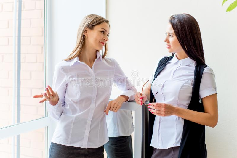 Two businesswomen telling gossip in an office stock photo