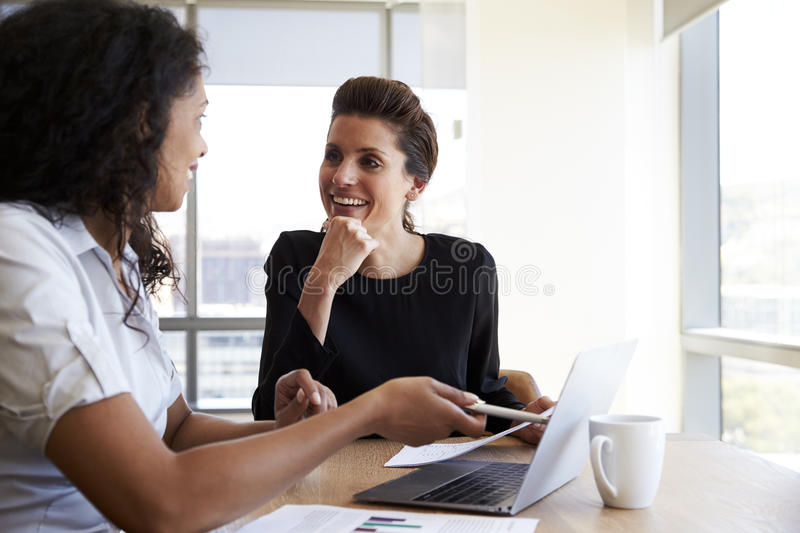 Two Businesswomen Using Laptop Computer In Office Meeting royalty free stock image