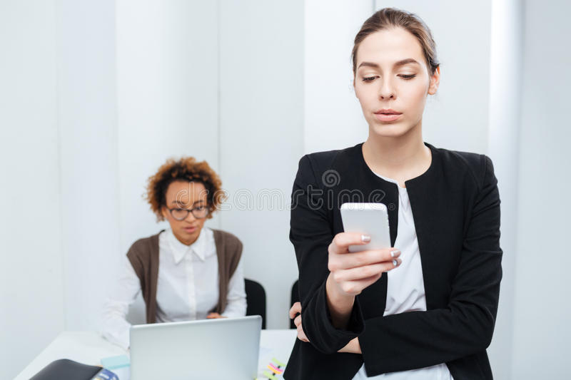 Two businesswomen using smartphone and laptop in office stock image
