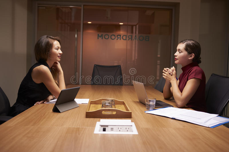 Two businesswomen working late sitting opposite each other stock images