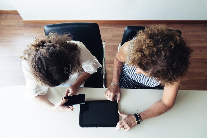 Two businesswomen working together at office. Top view. royalty free stock image