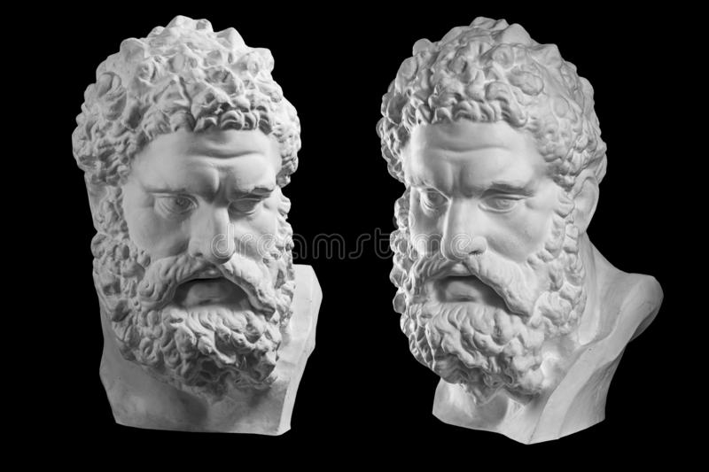 Two bust of Hercules. Heracles head sculpture, plaster copy of a statue isolated on black. Son of Zeus. Ancient statue. Two white bust of the Hercules. Heracles stock photography