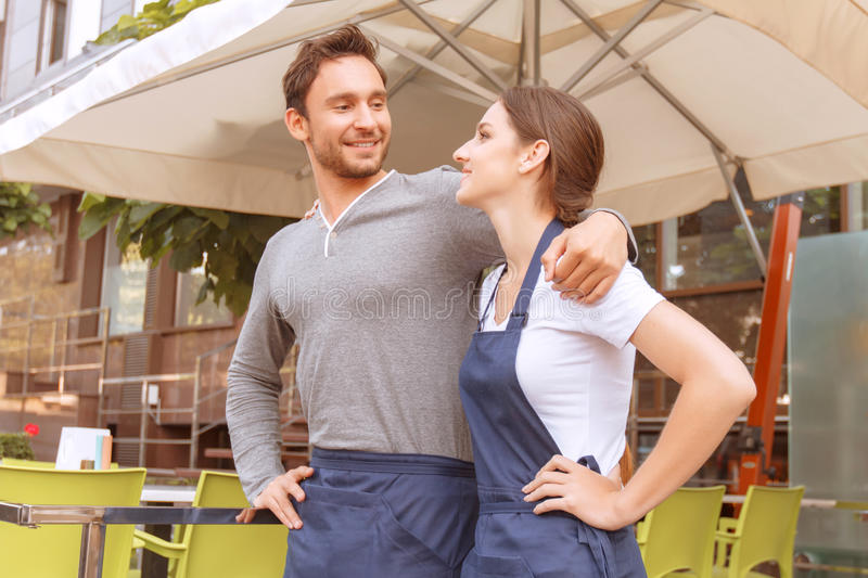 Two cafe workers standing outside. Friendly glance. Portrait of mail and female cafeteria workers standing outside cafe royalty free stock photo